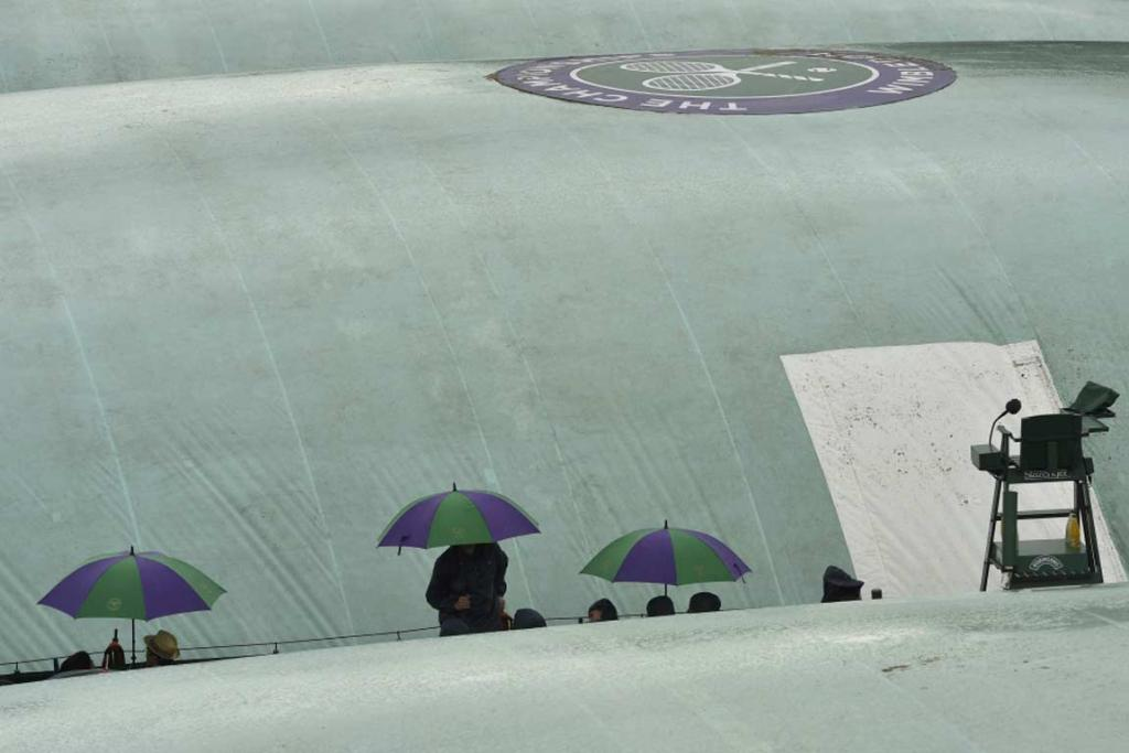 Spectators shield under umbrellas on the outside courts as rain disrupts play on day six.