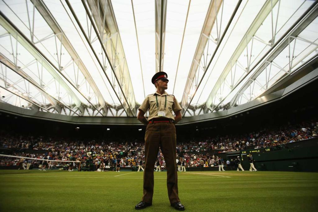 A security guard stands watch as the roof in closed due to rain on Wimbledon's centre court.