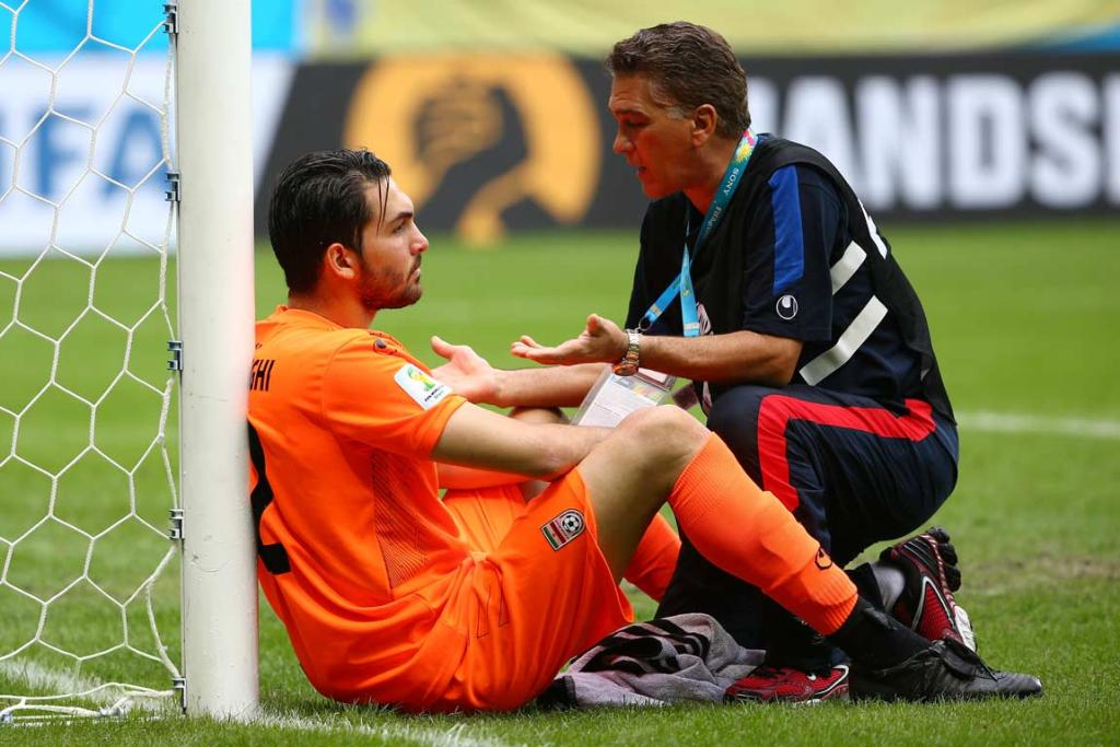 Iranian goalkeeper Alireza Hughighi is consoled by a member of the training staff after losing to Bosnia-Herzegovina.