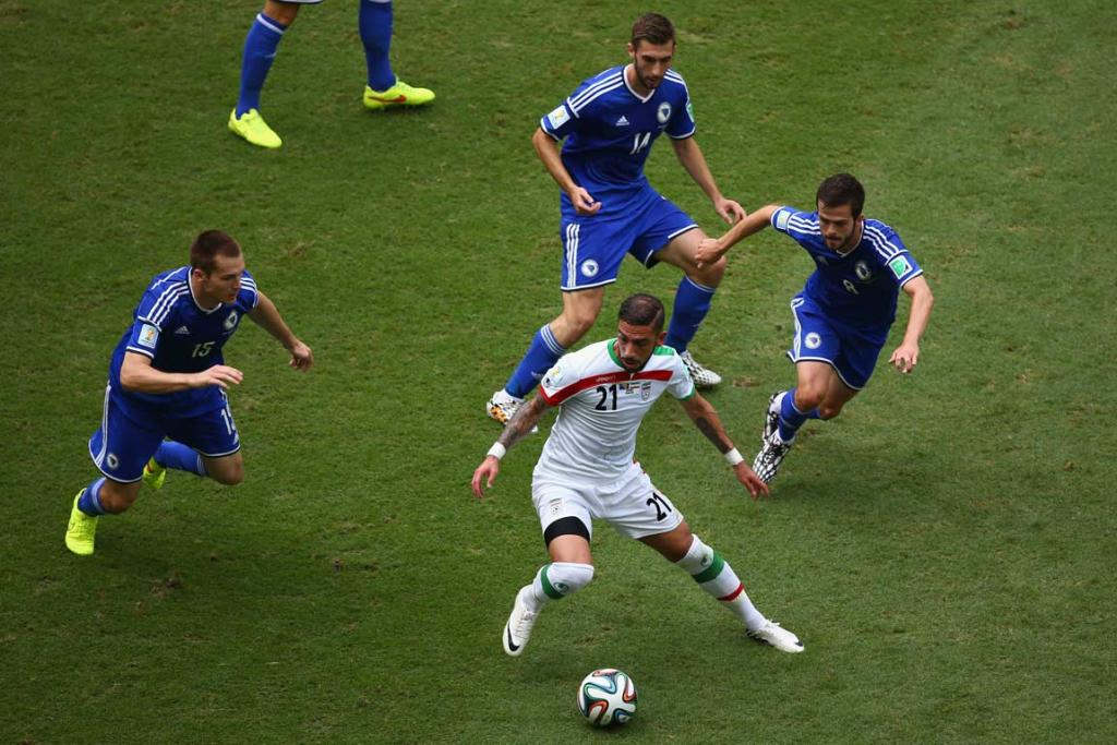 Iran's Ashkan Dejagah is surrounded by Toni Sunjic, Tino Sven Susic and Miralem Pjanic of Bosnia-Herzegovina.