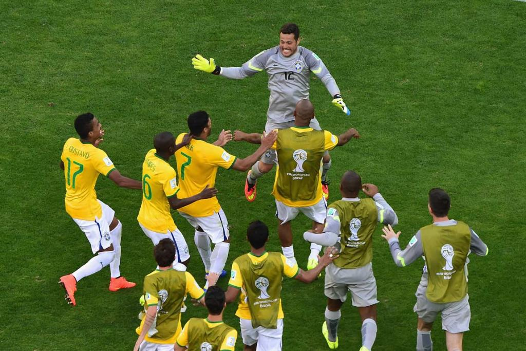 Brazilian players swarm to goalkeeper Julio Cesar after defeating Chile 3-2 in a penalty shootout.
