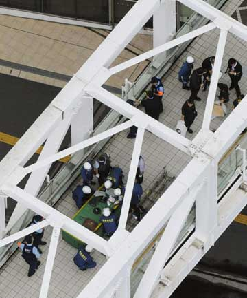 Police officers and fire-fighters investigate the site where a man set himself on fire at a pedestrian walkway near Shinjuku station in Tokyo.