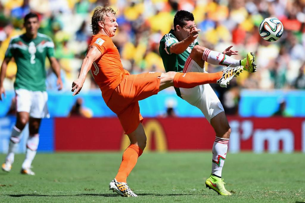 Holland's Dirk Kuyt battles for the ball with Mexico's Hector Herrera during their second round match in Fortaleza.
