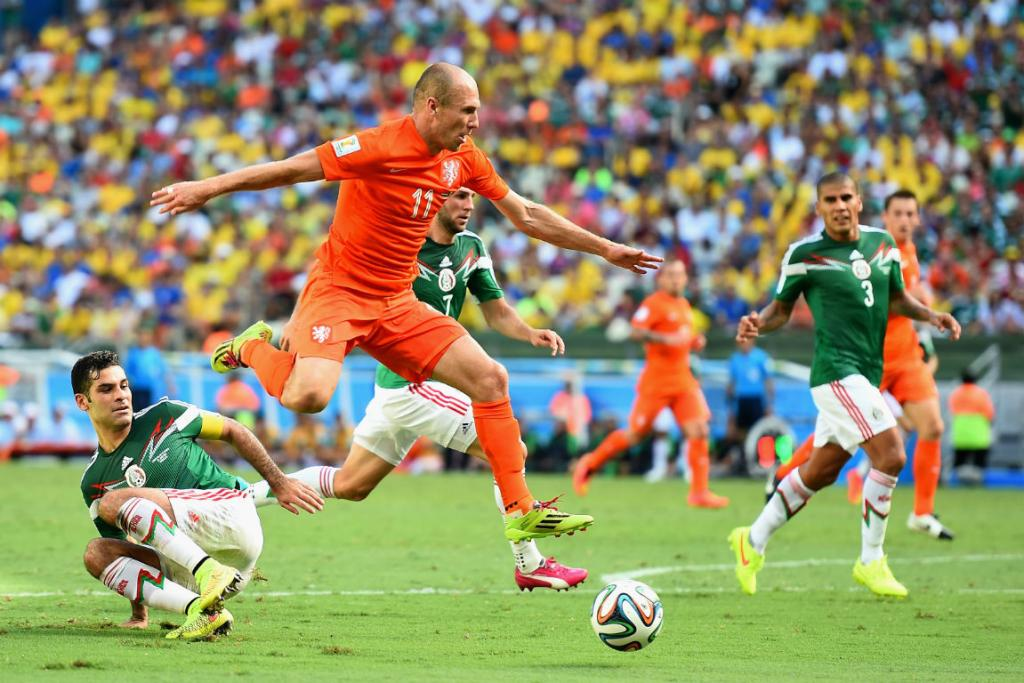 Dutch winger Arjen Robben rides the tackle of Mexico captain Rafael Marquez during his side's 2-1 win.