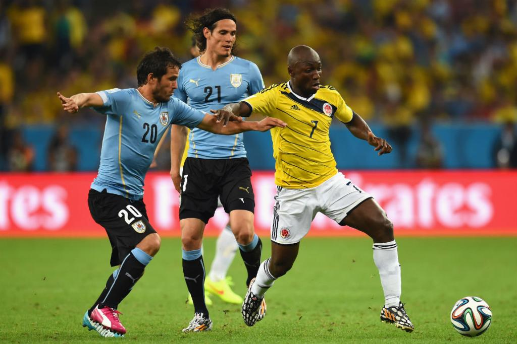 Uruguay's Alvaro Gonzalez challenges Colombia's Pablo Armero during their second round match at the Maracana in Rio de Janeiro.