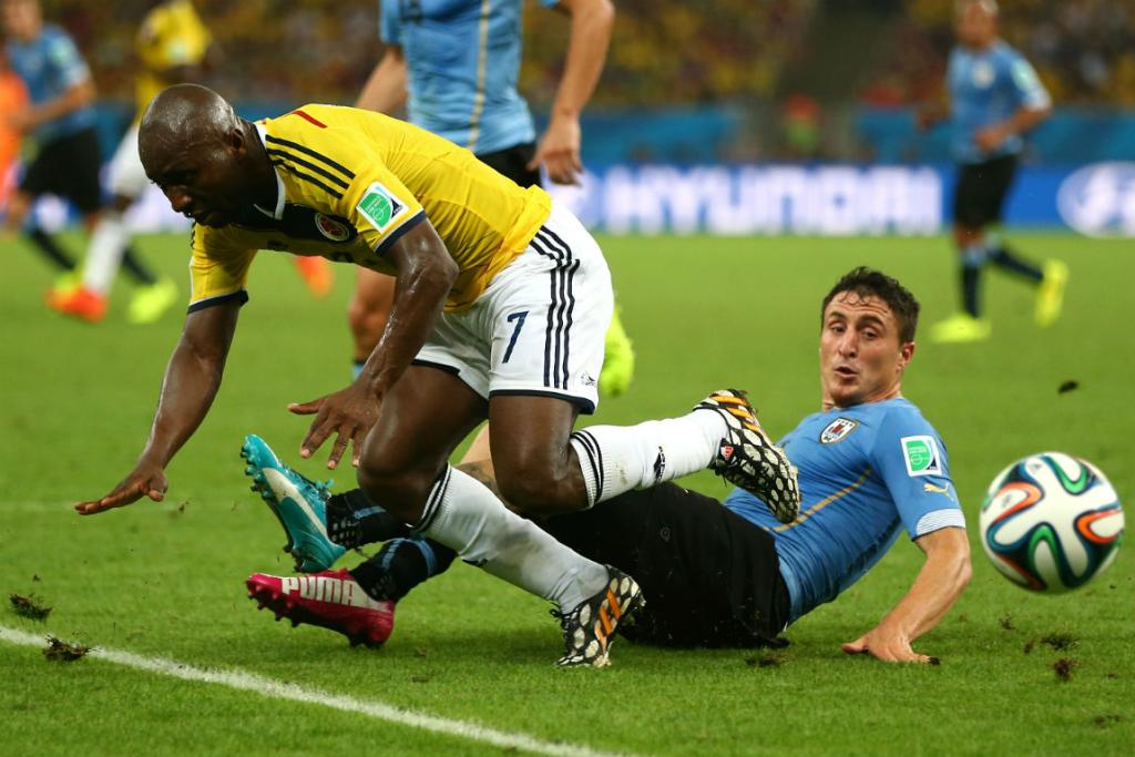 Uruguay midfielder Cristian Rodriguez tackles Colombia's Pablo Armero during their second round match in Rio de Janeiro.