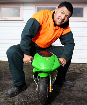 Sam Ekenasio, 20, on the mini motorbike he has put together to sell at the end of the year.