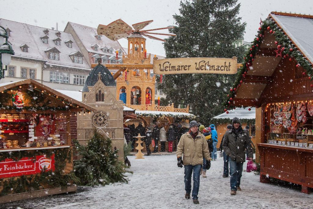 Experience a white Christmas: Snow falls on Weimar's Christmas Market in Germany.