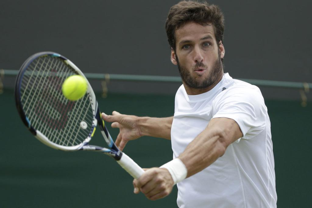 Feliciano Lopez of Spain hits a return to John Isner of the US during their men's singles match at Wimbledon.