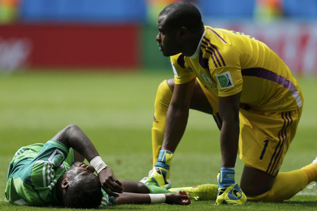 Nigeria's Vincent Enyeama (right) checks on teammate Ogenyi Onazi as he lies on the pitch after a challenge against France.