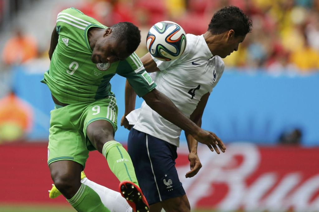 France's Raphael Varane is hit by the ball in the face beside Nigeria's Emmanuel Emenike (left).