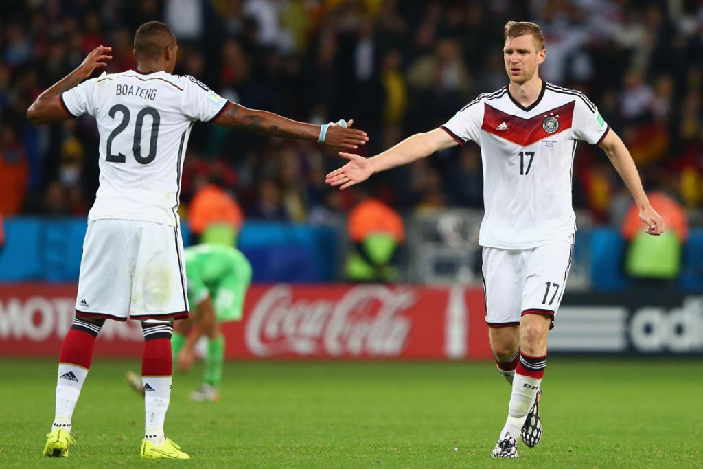 Jerome Boateng and Per Mertesacker of Germany celebrate their team's second goal in extra time against Algeria.