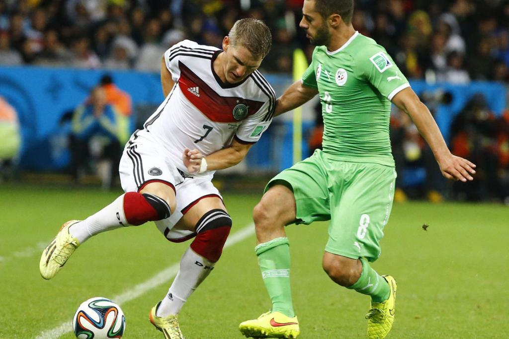 Germany's Bastian Schweinsteiger (left) fights for the ball with Algeria's Mehdi Lacen during extra time round of 16 game at the Beira Rio stadium in Porto Alegre.