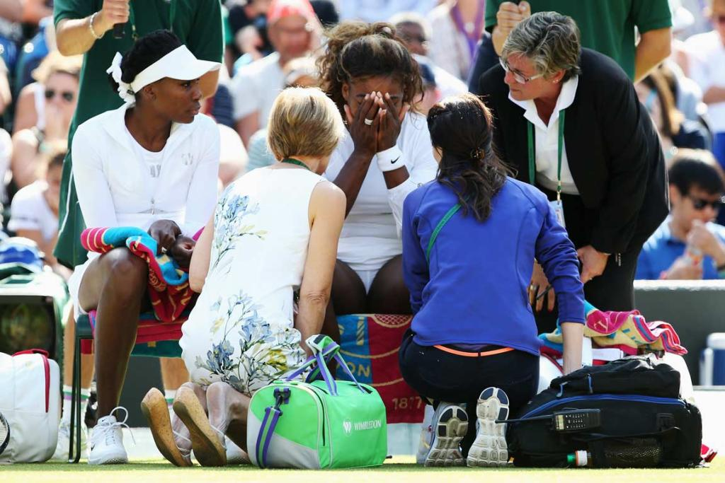 Serena Williams is treated by medical staff before a women's double match with sister Venus (left).