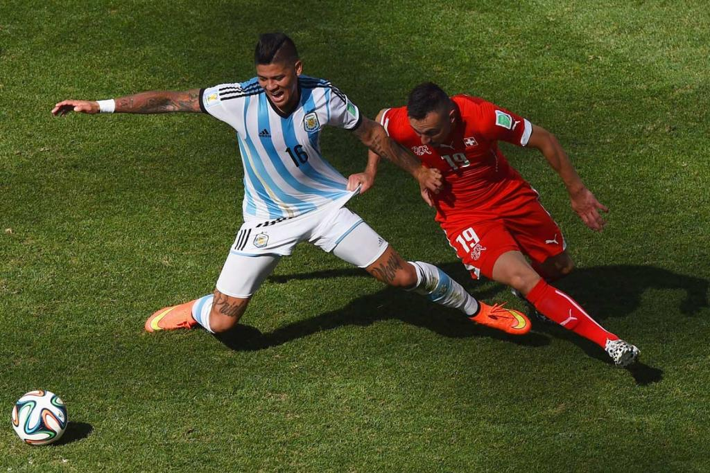 Argentina's Marcos Rojo jostles with Switzerland's Josif Drmic for possession in Sao Paulo.