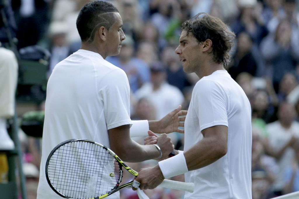 Nick Kyrgios of Australia (left) shakes hands with Rafael Nadal of Spain after defeating him in their men's singles tennis match at Wimbledon.