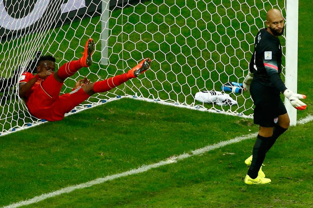 Belgium's Divock Origi throws himself into the goal net, behind USA goalkeeper Tim Howard after narrowly missing a strike.