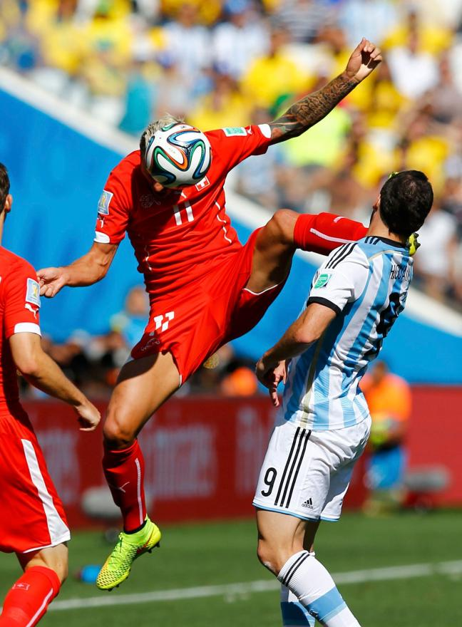 Switzerland's Valon Behrami jumps for the ball next to Argentina's Gonzalo Higuain.