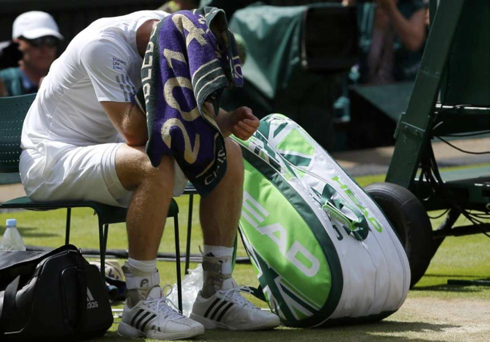 Andy Murray sit dejected with a towel over his head after his Wimbledon title defence ended in the quarterfinals.