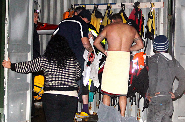 Members of the Otaikokako Waka Ama Club in New Plymouth warm up in their shed after their brush with disaster.