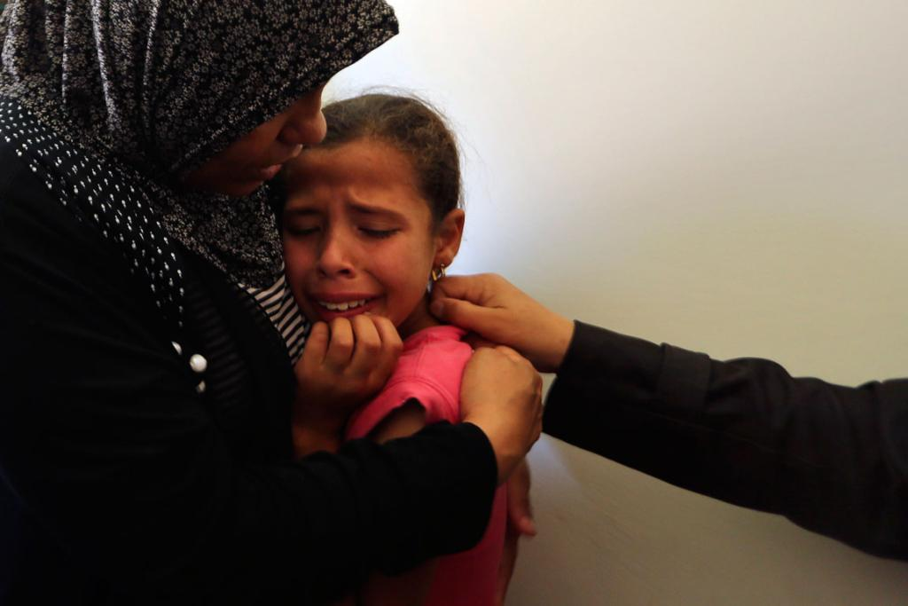 Al-Danaf's sister is comforted at the funeral.