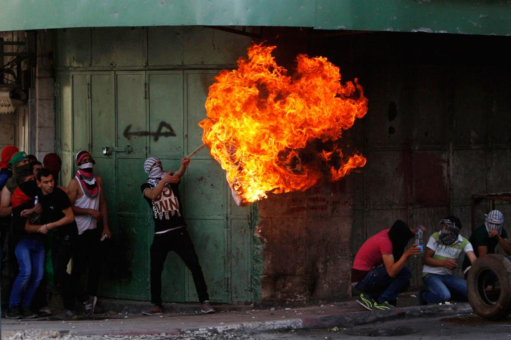 An Israeli flag is burnt by Palestinian protester.