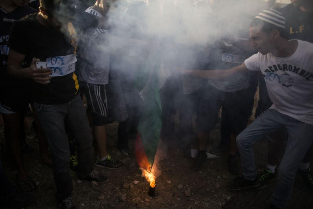 A Palestinian flag is burnt by Israeli protesters.