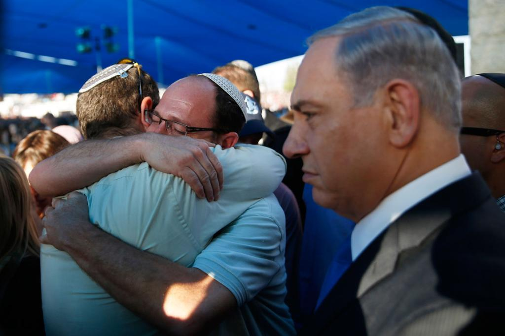 Here, two of the fathers embrace besides Israeli Prime Minister Benjamin Netanyahu.