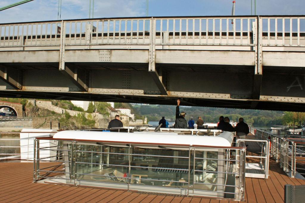 Passengers stand trying to touch a bridge as the Viking Freya cruises down the Danube River.