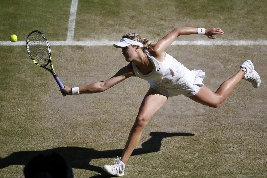 Eugenie Bouchard of Canada hits a return during her women's singles semi-final match against Simona Halep of Romania at Wimbledon.