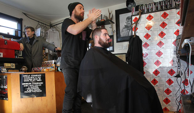 Levon Maeder, left, and Criss Hathaway, doing the hair of Ben Scott, are business partners operating Hello My Name is Barber