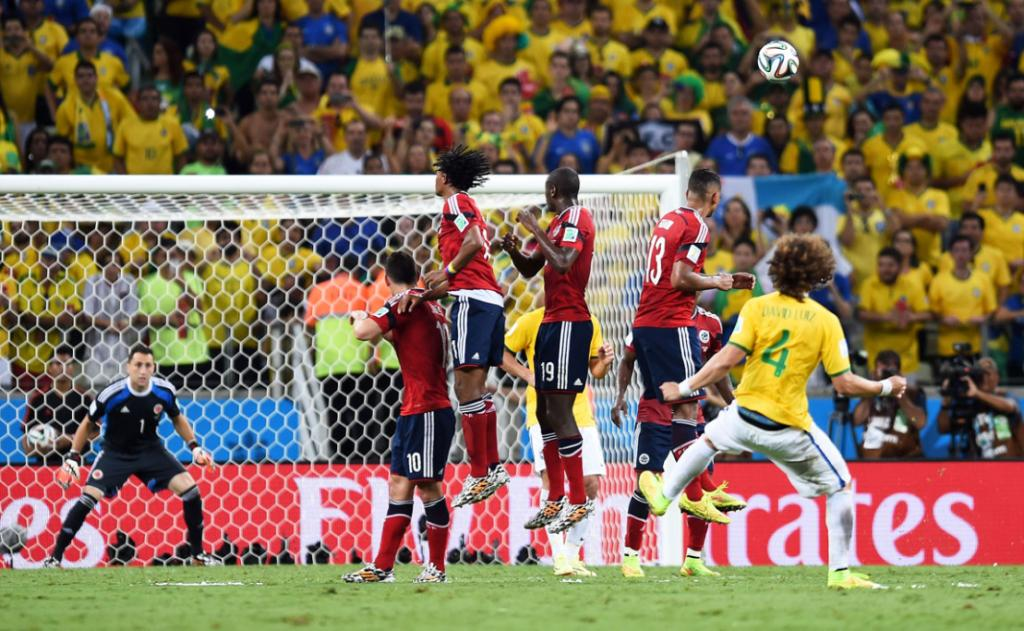 WATCHING HIS WORK: Brazil's David Luiz looks on in hope as his free-kick travels toward the net - it goes in to give the World Cup hosts a 2-1 lead in the quarterfinal against Colombia.