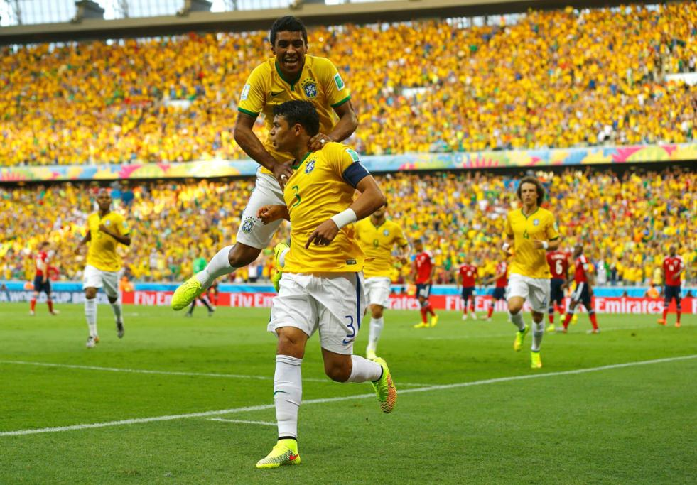 GREAT GOAL: Brazil's Paulinho leaps onto his captain Thiago Silva to celebrate the opening goal of their quarterfinal against Colombia.