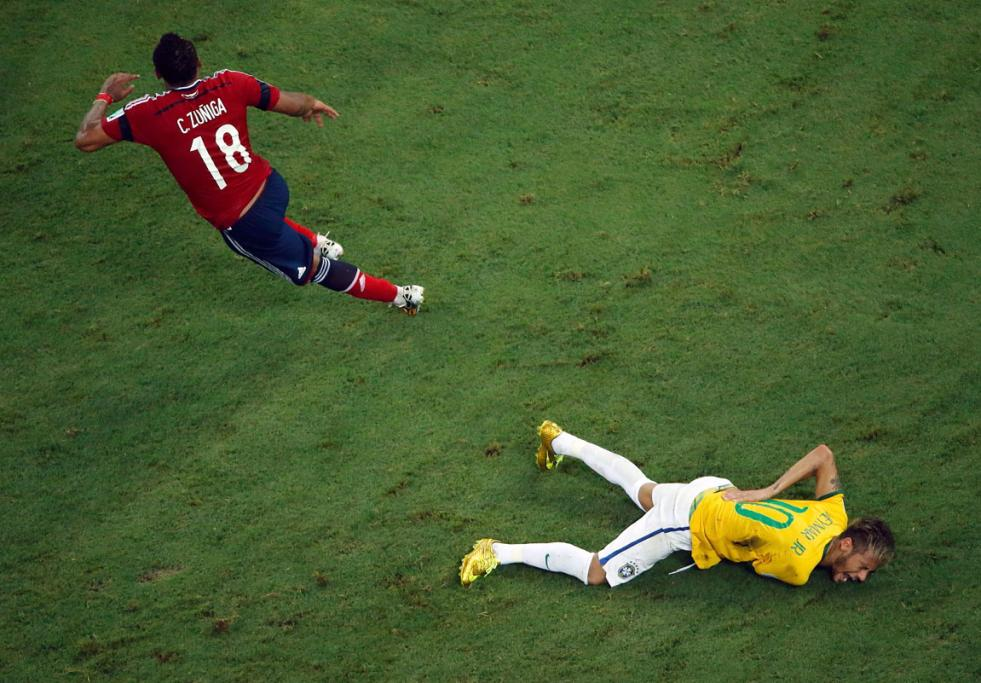 OUCH: Brazil star Neymar clutches his back after a challenge from Colombia's Camilo Zuniga. He was carried off on a stretcher and taken to hospital.