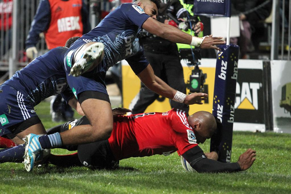 Nemani Nadolo crashes over the line for the Crusaders under pressure from a stern Blues defence.