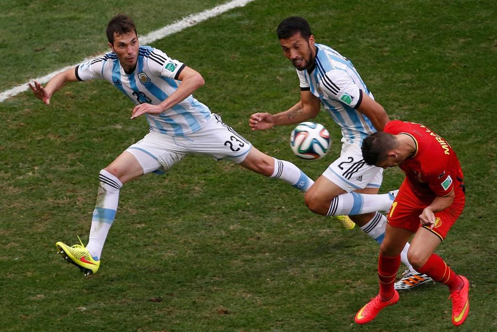 Belgium's Kevin Mirallas heads the ball narrowly wide as Argentina's Jose Basanta and Ezequiel Garay look on.