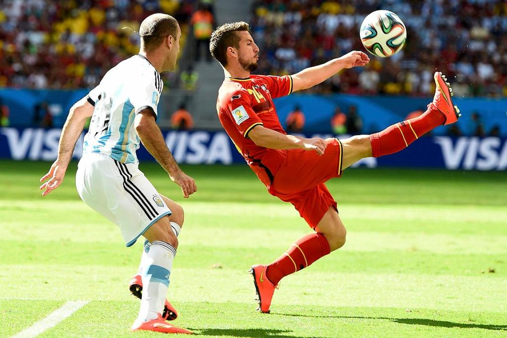 Argentina's Rodrigo Palacio watches as Belgium's Dries Mertens makes contact.