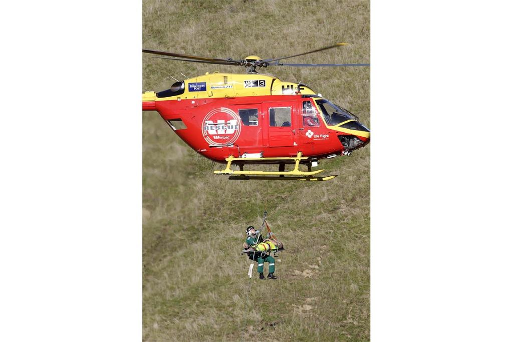 The Westpac rescue helicopter winches a hunter up from the site of the crash.