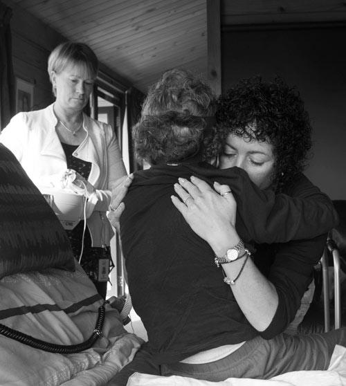 Hospice - Nurse Cathy Mills (back) assists while Tania Merrilees helps her mother  Diane Blackburn sit down.