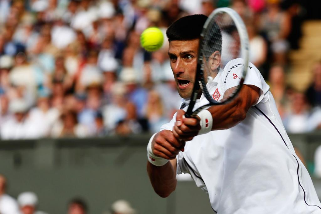 Novak Djokovic of Serbia plays a backhand return to Roger Federer of Switzerland during the men's singles final at Wimbledon.