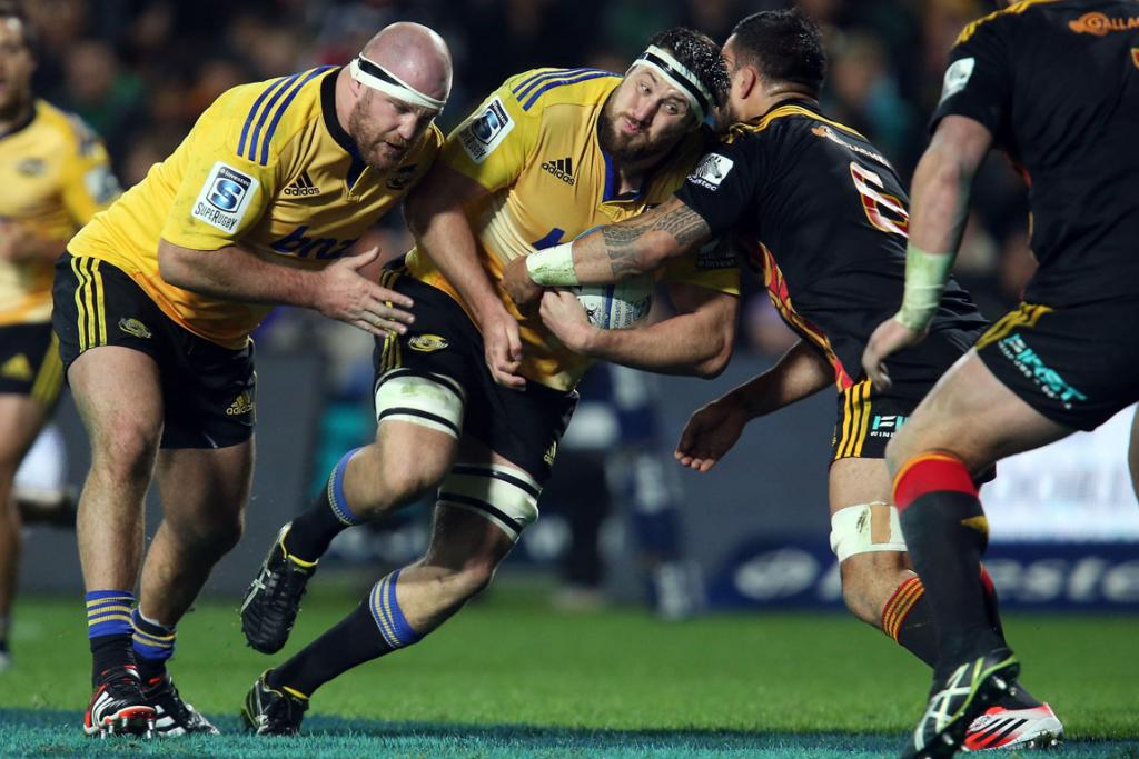Jeremy Thrush of the Hurricanes charges into Liam Messam of the Chiefs with the assistance of Ben Franks (left) during the round 18 clash between the two sides at Waikato Stadium in Hamilton.