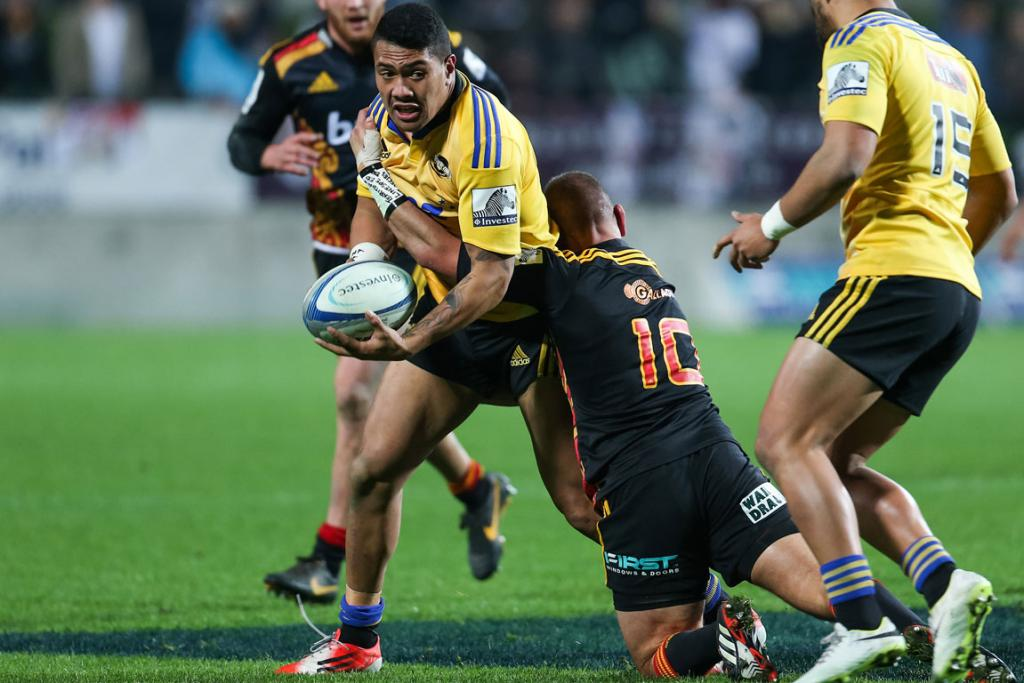Ardie Savea of the Hurricanes is tackled by Chiefs captain Aaron Cruden during the round 18 fixture at Waikato Stadium.