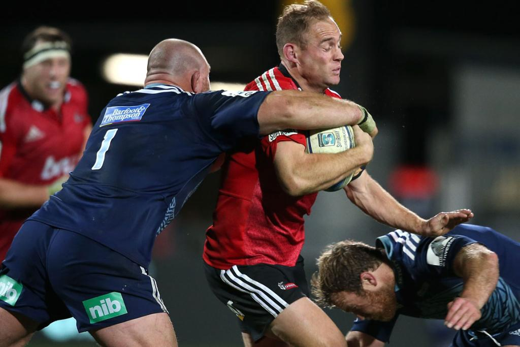 Andy Ellis, centre, of the Crusaders is tackled by Blues players Tony Woodcock (left) and Luke Braid (right) during his side's win in Christchurch.