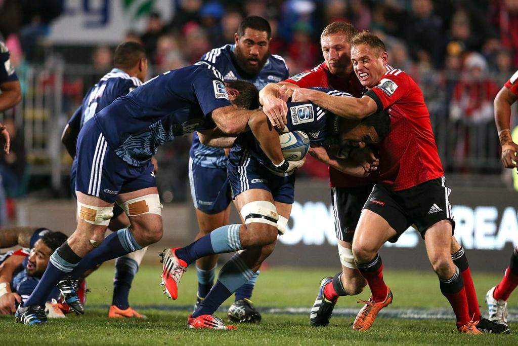 Jerome Kaino of the Blues is tackled by Andy Ellis of the Crusaders during their round 18 Super Rugby match in Christchurch.