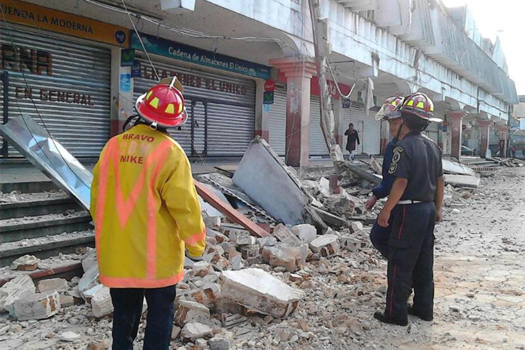 Municipal firefighters stand outside a damaged building in the San Marcos region, in the northwest of Guatemala, in this July 7, 2014 handout picture by Guatemala's municipal fire department.
