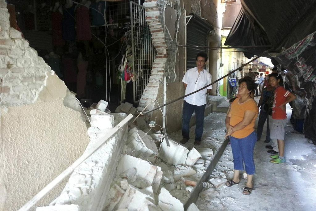 Residents stand next a building damaged by an earthquake in the town of Huixtla, Mexican state of Chiapas.