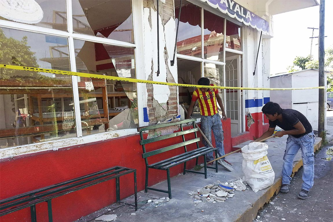Residents clean up debris at a restaurant damaged by an earthquake in the town of Huixtla, Mexican state of Chiapas.