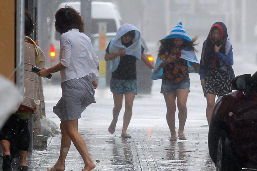 Women walk in strong winds caused by typhoon Neoguri at Kokusai street, a shopping and amusement district in Naha, on Japan's southern island of Okinawa.