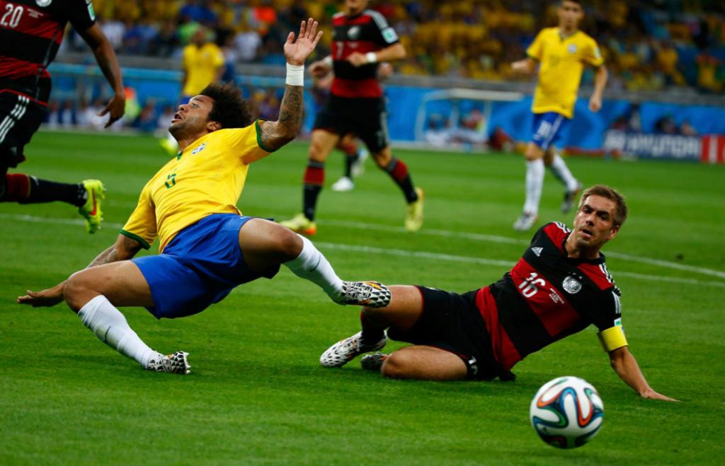 Marcelo is swept off his feet by a sliding tackle by Germany captain Philipp Lahm.