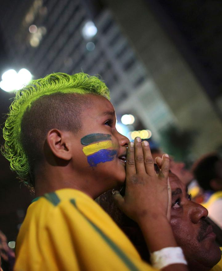 A boy looks on in disbelief after his team Brazil is beaten 7-1 in the World Cup semifinals.
